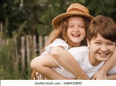 Happy children with piggyback riding in sunset light. Girls laugh. Friendship concept .