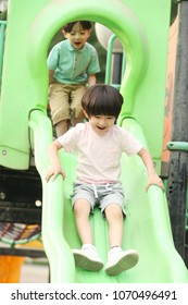 Happy children play the slides outdoors