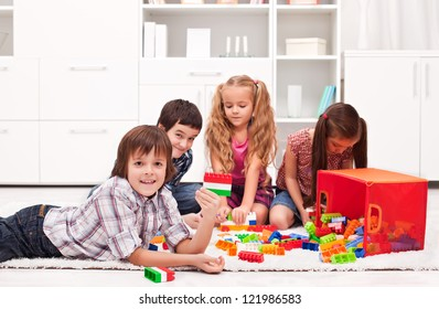 Happy children playing with blocks - focus on the boy
