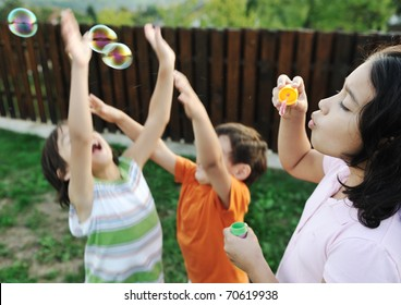 Happy children playing with bubbles outdoor, selective focus - kids in motion