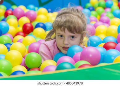 Happy children playing and having fun at kindergarten with colorful balls, a child in the pool with balls.