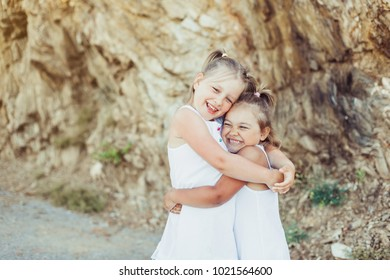 Happy children playing hugging near the mountain. Kid having fun outdoors. Summer vacation and healthy lifestyle concept