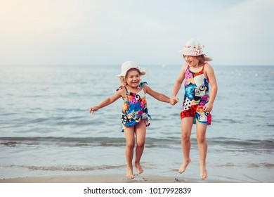 Happy children playing, jumping and holding hands on the beach coast. Kids sisters having fun outdoors. Summer vacation and healthy lifestyle concept