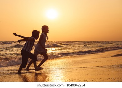 Happy children playing on the beach at the sunset time.Two Kids having fun outdoors. Concept of summer vacation and friendly family.
