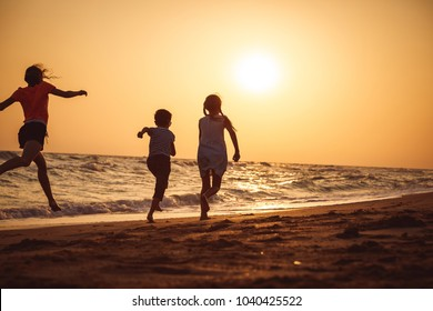 Happy children playing on the beach at the sunset time. Three Kids having fun outdoors. Concept of summer vacation and friendly family.
