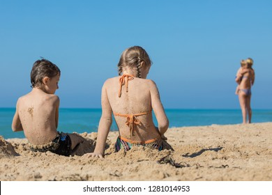 Happy children playing on the beach at the day time. Two Kids having fun outdoors. Concept of summer vacation and friendly family.