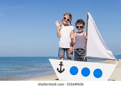 Happy children playing on the beach at the day time. Concept of happy friendly family.