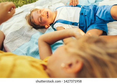 Happy children playing on the blanket outdoors. Happy little boy and cute little girl relaxing in the park. Kids having fun on sunlight. Sister and brother spending time together