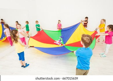 Happy children playing parachute games in gym