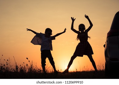 Happy children playing in the park at the sunset time. People having fun outdoors. Concept of summer vacation and friendly family.