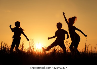 Happy children playing in the park at the sunset time.