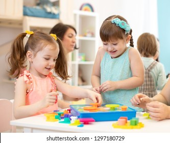 Happy children playing with plastic building blocks at kindergarten