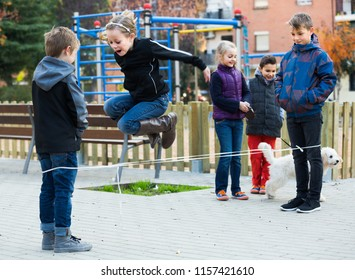 Happy children playing rubber band jumping game and laughing in park