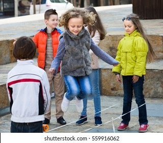Happy children playing rubber band jumping game and laughing outdoors