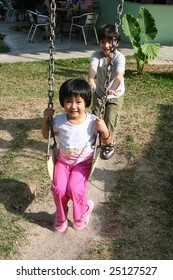 Happy children playing swing at the playground in the park on sunny day