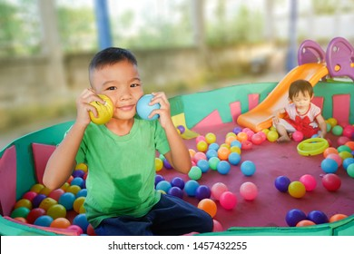Happy children playing with the toys ball at the kindergarten. A young boy smiling and holding many ball in his hands with baby sister.