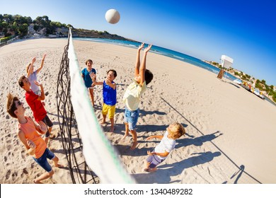 Happy children playing volleyball on the beach