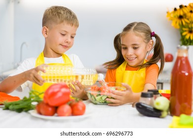 Happy children pour sunflower oil in a salad in the kitchen