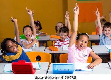 Happy children raising their hands in classroom