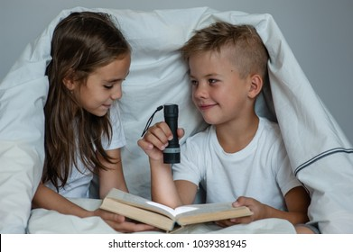 Happy children read the book under the blanket
