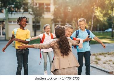 Happy children running into hug of their teacher.