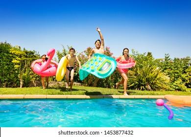 Glückliche Kinder laufen und springen ins Schwimmbecken
