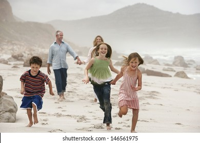 Happy children running on beach with parents walking in background