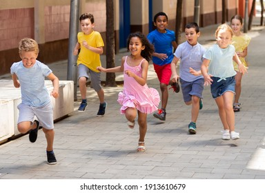 Happy children running in race and laughing outdoors at sunny day