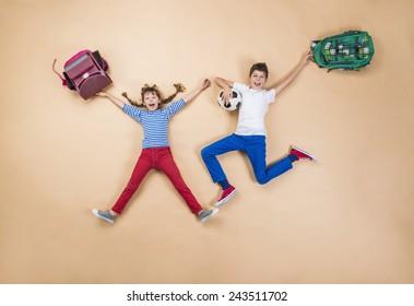 Happy children running to school in a hurry. Studio shot on a beige background.