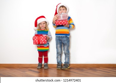 Happy children in Santa red hats holding Christmas presents on a white background. Christmas time.