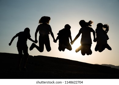 Happy children shadows jumping at sunset. holiday and vacation concept.