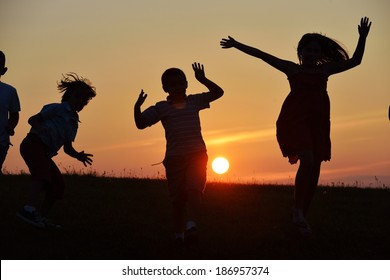 Happy children silhouettes on summer meadow running and jumping