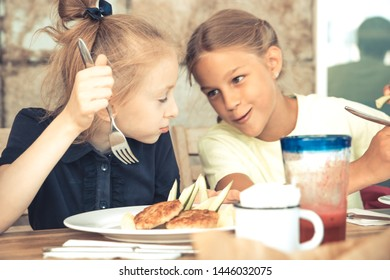 Happy children sister girls having a rest time in cafe restaurant talking together childhood lifestyle