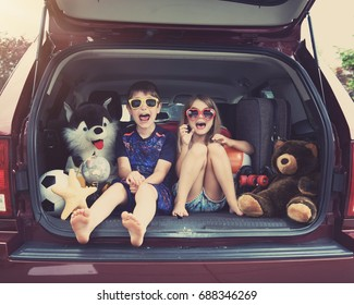 Happy Children are sitting in the back of a car with travel objects waiting to go on a vacation. Use it for a family holiday lifestyle concept.