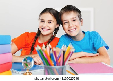 Happy children sitting by the table during