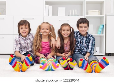 Happy children sitting on the carpet wearing colorful socks