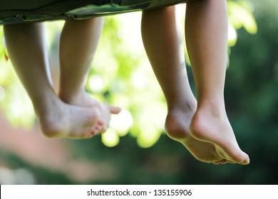 Happy children sitting on green grass outdoors in summer park