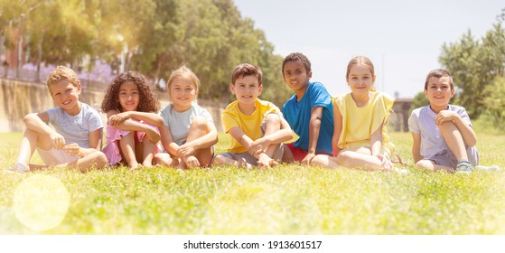 Happy children sitting on the green grass on a sunny day