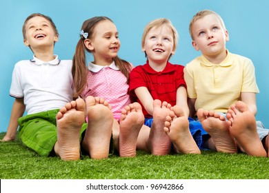 Happy children sitting on the lawn barefoot