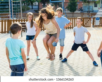 Happy children skipping on chinese jumping elastic rope in yard