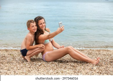 happy children with the smartphone on a beach