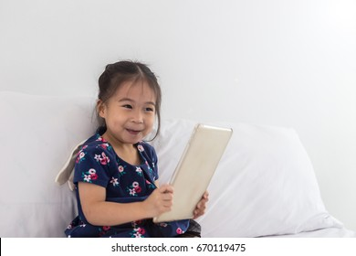 Happy Children smile with tablet in bedroom