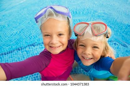 Happy children with  snorkeling equipment making selfie in swimming pool