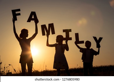 """Happy children standing on the field at the sunset time. They keep the letters forming the word """" family"""". Concept of friendly family."""