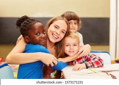Happy children as a student hug their educator in kindergarten or school