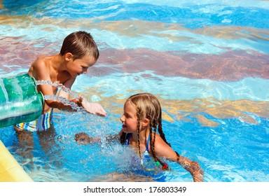 Happy children in the summer outdoor pool.