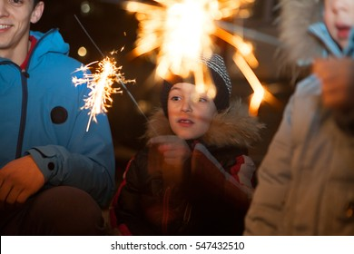 Happy children and them father with fireworks in his hands.