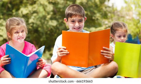 Happy children of three sitting on grass with books