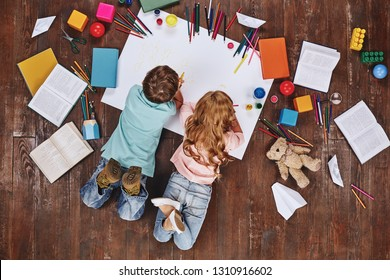 Happy children. Top view creative photo of little boy and girl on vintage brown wooden floor. Children lying near books and toys, while drawing