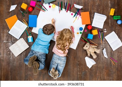 Happy children. Top view creative photo of little boy and girl on vintage brown wooden floor. Children lying near books and toys, and painting - Shutterstock ID 393638731